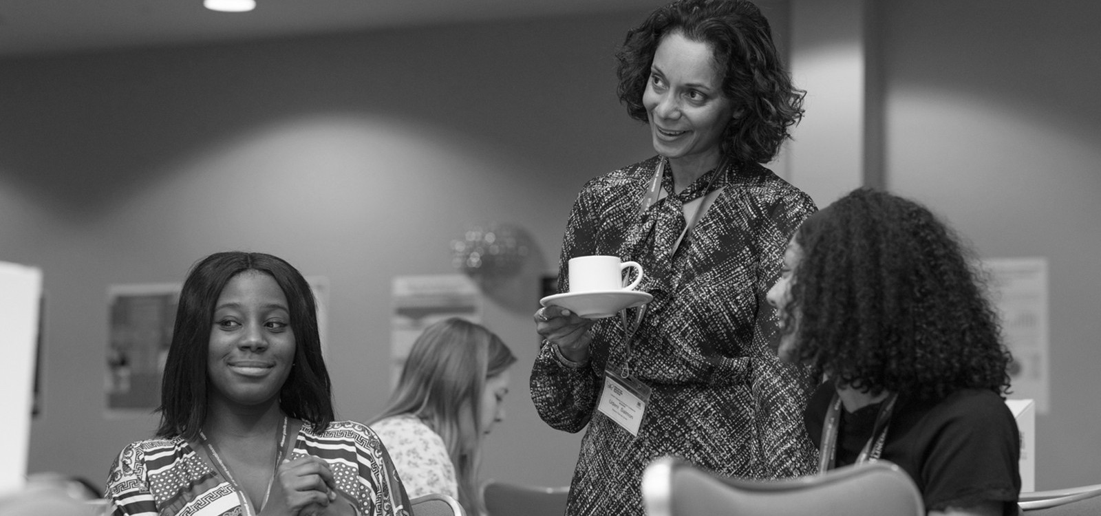 A racially diverse group of researchers chatting over coffee, depicting collaborative working