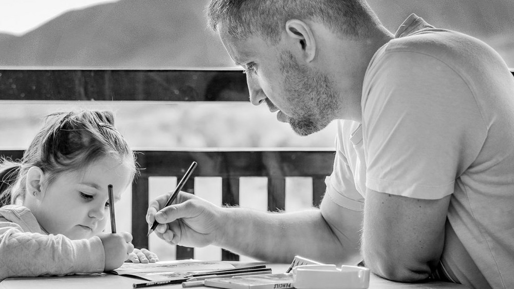 White father teaching his small daughter how to write. Outside, sunshine, happy